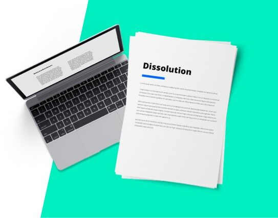 Next to a laptop, a document with the word dissolution printed on it.