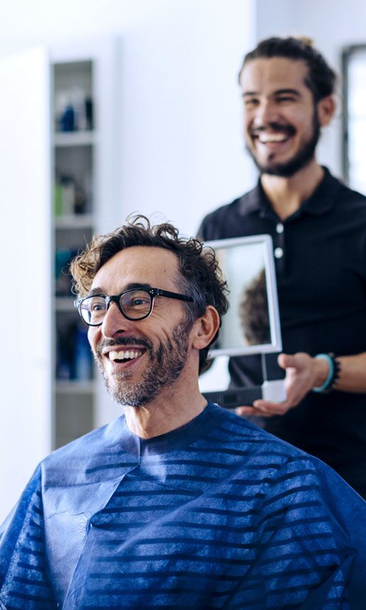 A smiling hairdresser shows haircut to client.