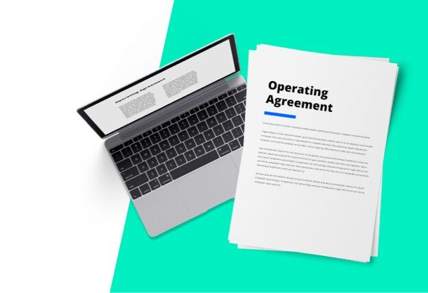Next to a laptop, a document with the words operating agreement printed on it.