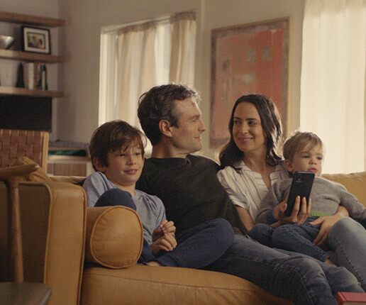 Mom and dad smiling on the couch with their kids as they create their estate plan on a smartphone