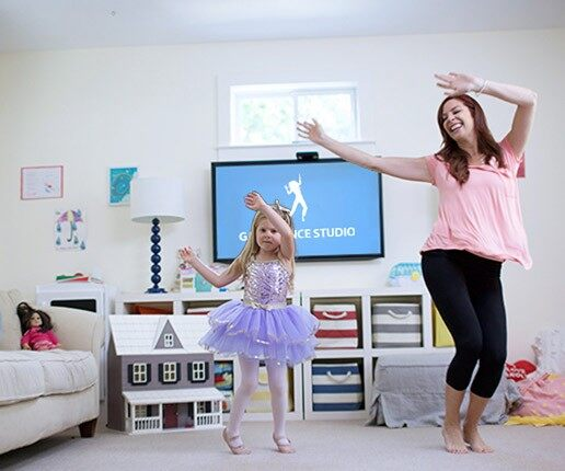 A mom and her daughter dancing in their living room.