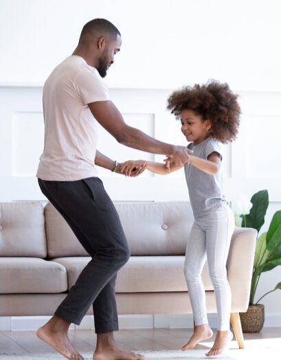 A dad teaches his young daughter to dance.