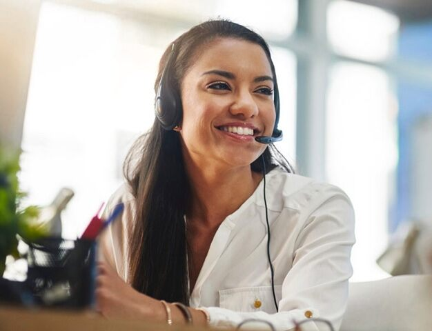 Woman in customer care on phone headset smiling.