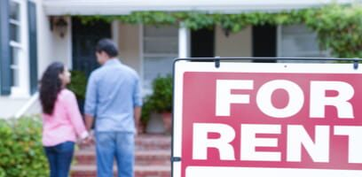 Couple viewing home with 'for rent' sign in front