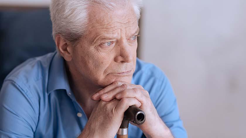 elderly man rest chin on cane