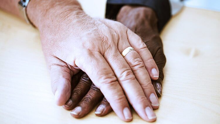 aged couple hands with wedding bands