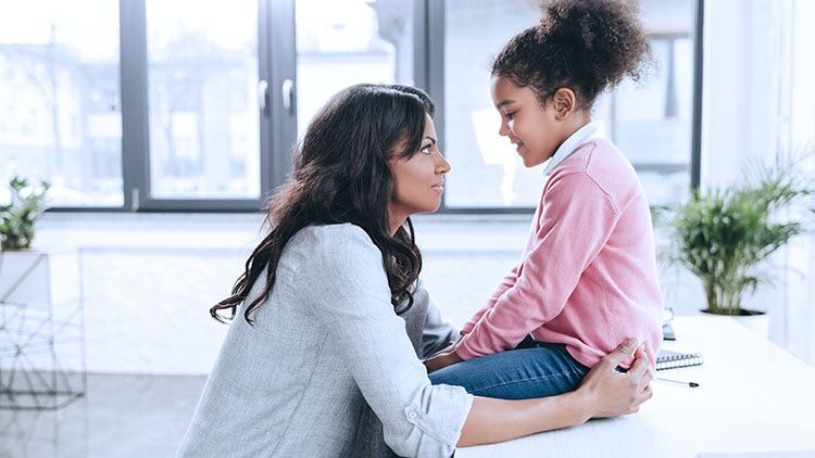 Mother having serious talk with young daughter