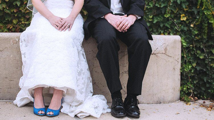 Bride and groom sit side by side in wedding clothes