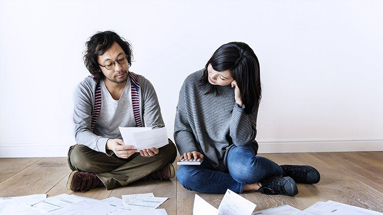 Man and woman look over bills and calculate costs