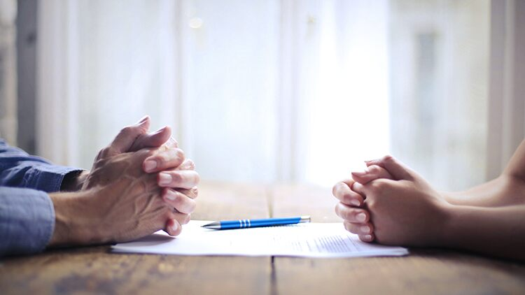 Man and woman face each other hands closed on table