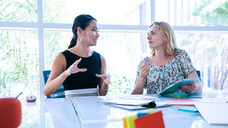 Two woman talking business plans