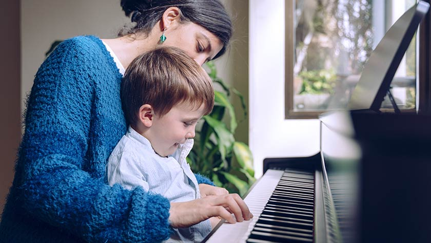 Mother holding child on lap playing piano