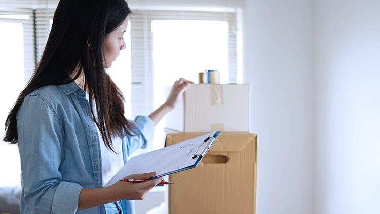 Woman holding clipboard looking at boxes