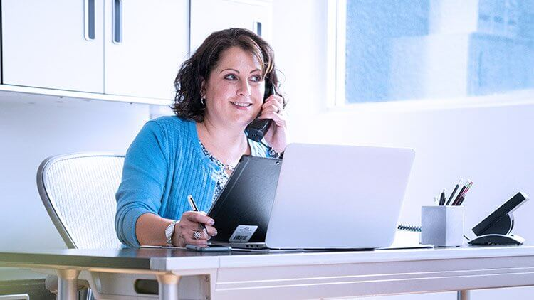 woman smiling on phone in office at desk