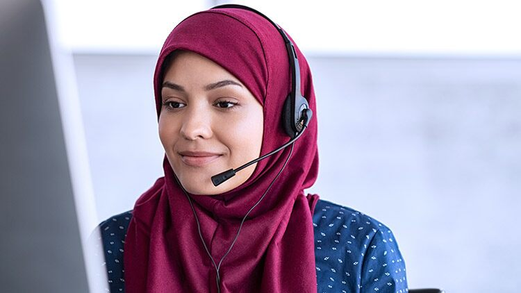 woman-wearing-headset-smiles-looking-at-monitor 1