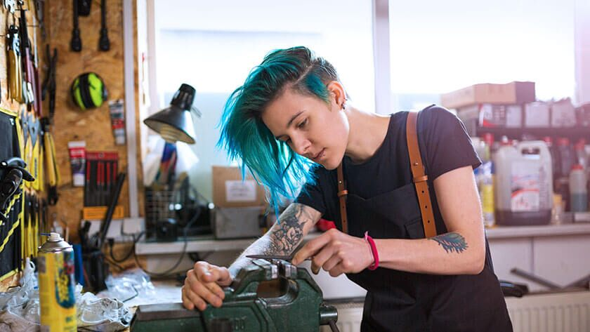 woman-with-blue-hair-working-in-hardware-shop in black shirt and suspenders