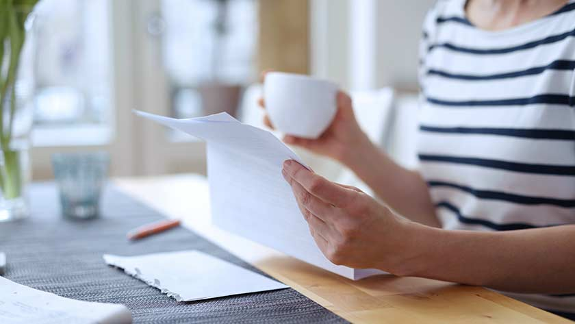 Woman at home drinking coffee and looking over letter