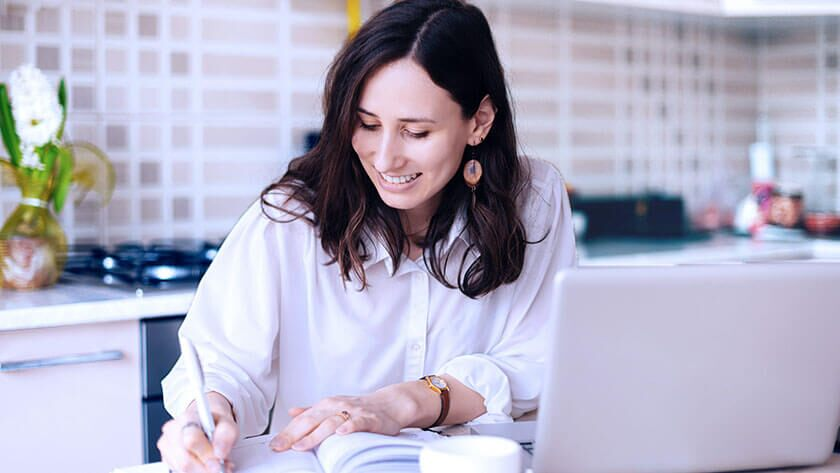 woman-writing-notes-in-kitchen-using-laptop in white shirt