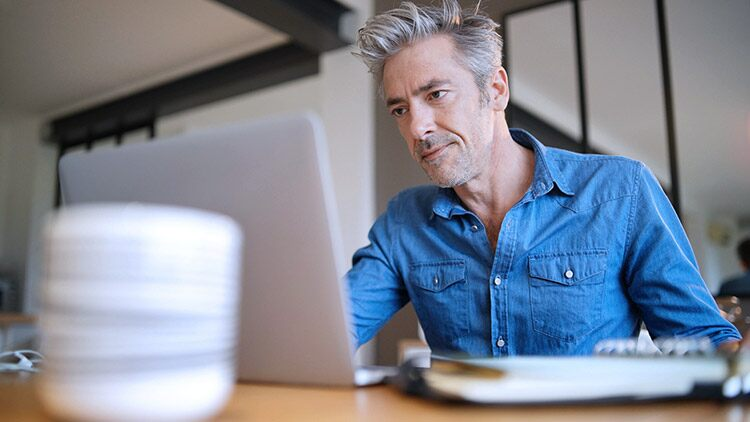Older man serious looks at computer