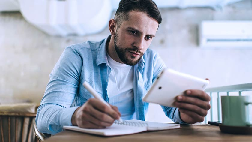 Man writing notes looking at mobile phone