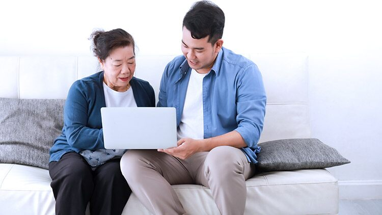 Senior mother and adult son sit on sofa looking at laptop