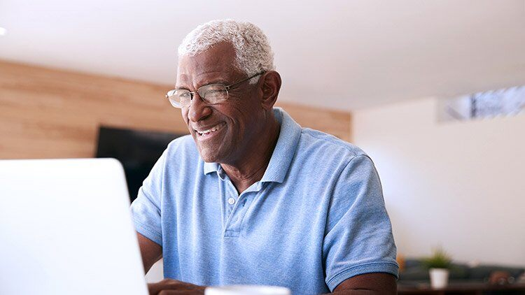 Senior man looks at laptop smiling