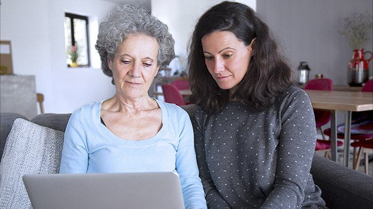 Senior mother and adult daughter look at computer