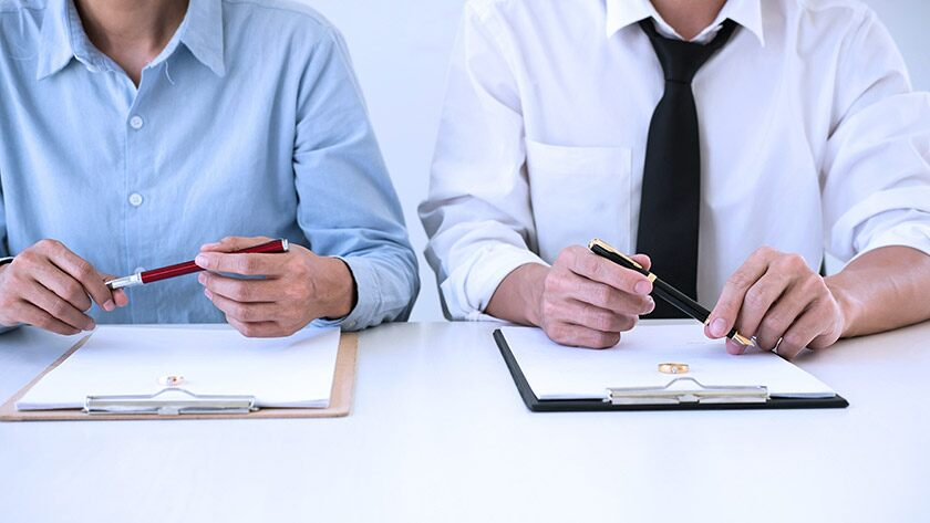 Woman and man side by side signing contracts