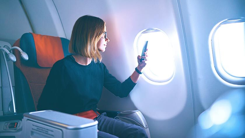 woman-on-plane-using-mobile
