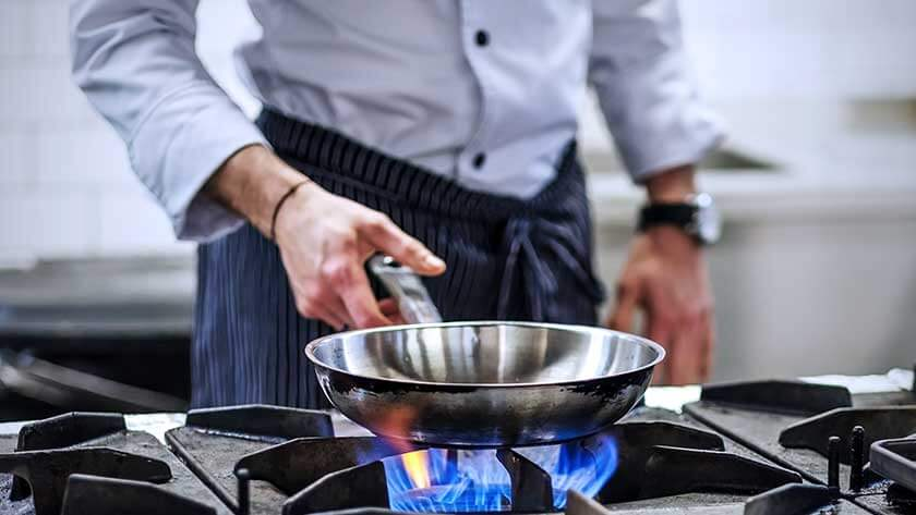man-holding-pan-over-fire-stove in commercial kitchen