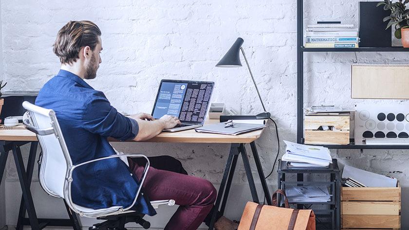 man-sitting-in-home-office-using-laptop wearing blue shirt
