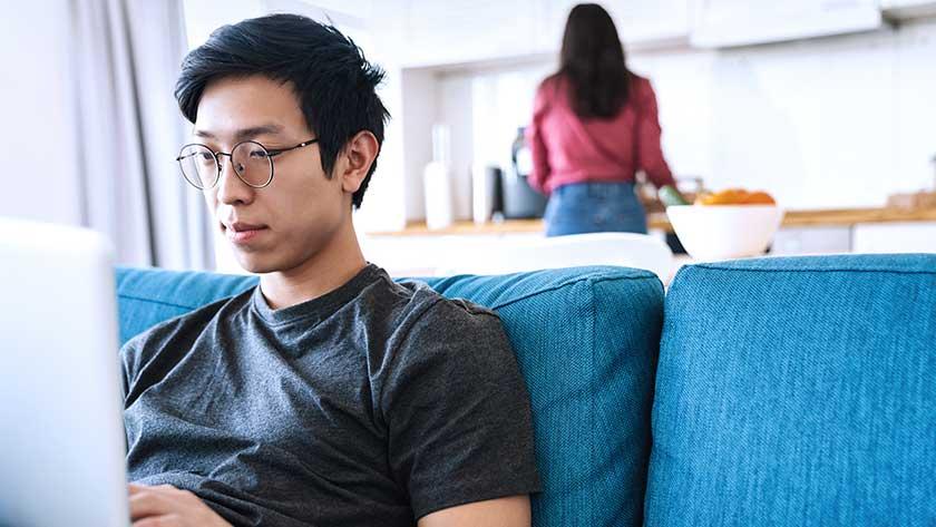 man-sitting-on-sofa-looking-at-laptop