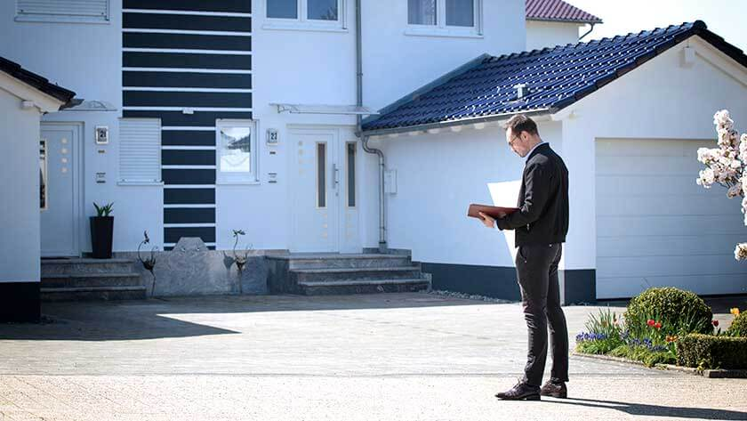 man-standing-outside-home-with-clipboard