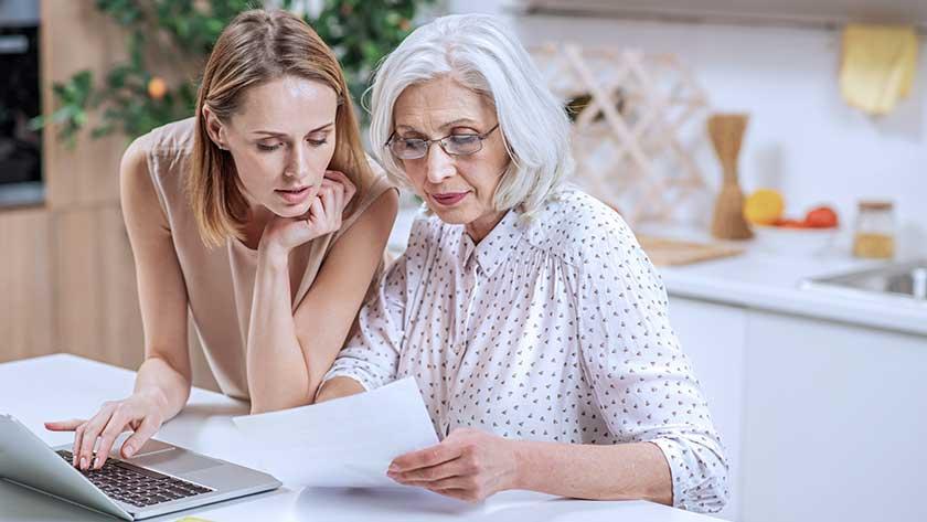 elderly woman and daughter looking over paperwork