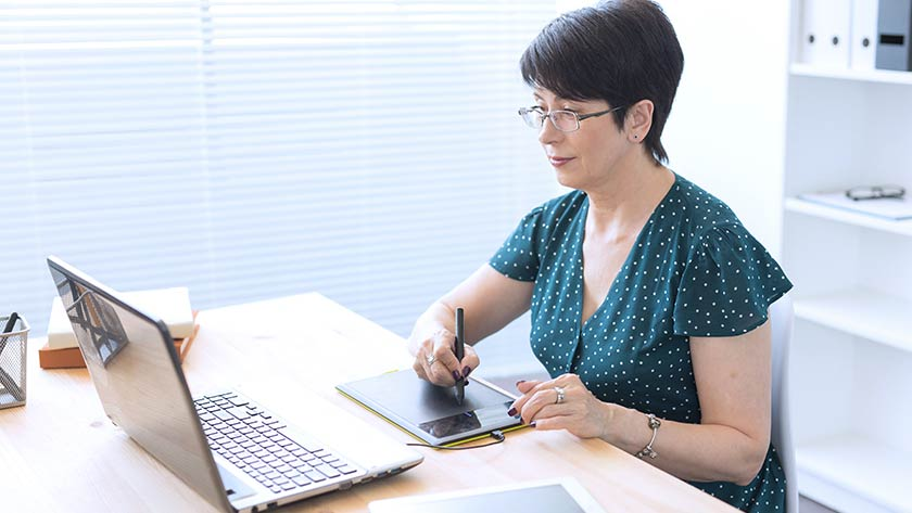 woman-working-at-desk-on-laptop-using-stylus