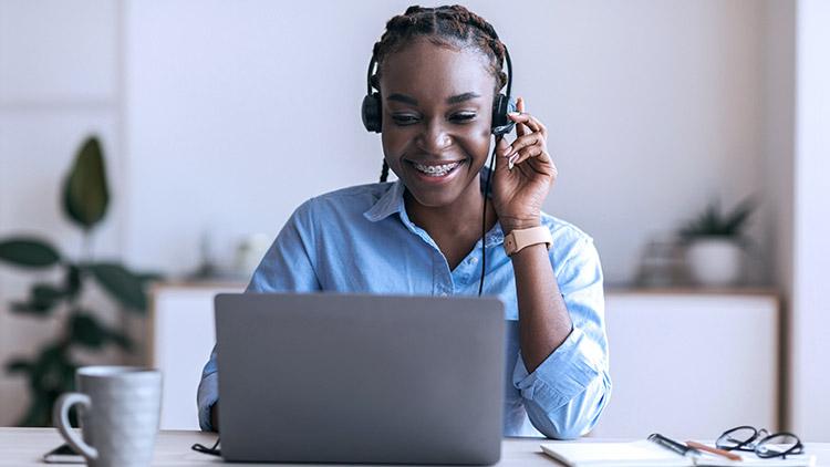 women-wearing-headset-looking-at-laptop-smiling