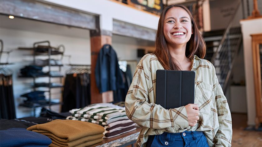 woman in retail store smiling holding a tablet