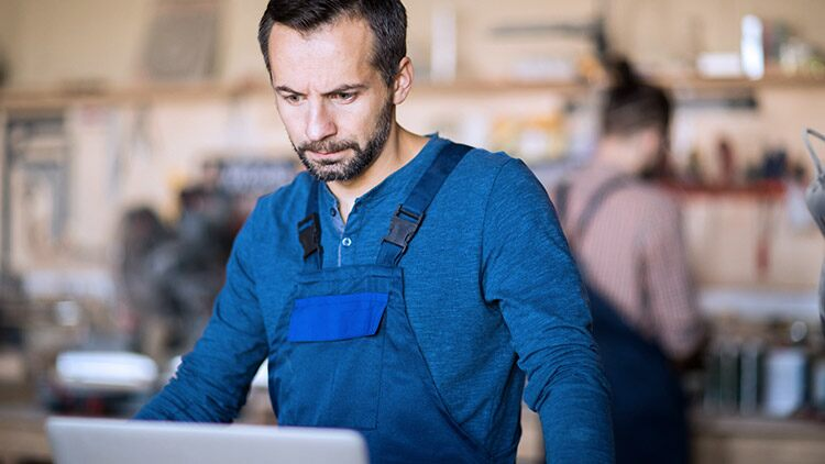man-in-woodworking-shop-looks-at-computer